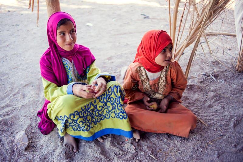 Egypten Hurghada, 12 kan 2019, två små flickor som sitter på jordningen i den beduin- byn royaltyfria foton