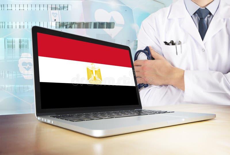 Egypten vårdsystem i techtema Egyptisk flagga på datorskärmen Doktor som står med stetoskopet i sjukhus fotografering för bildbyråer
