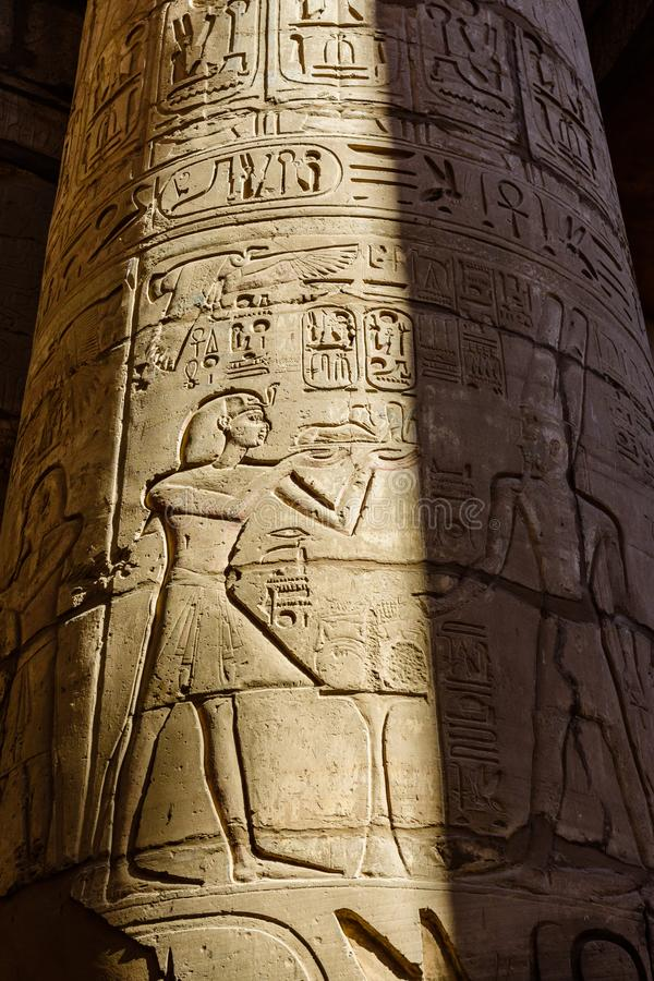 Egyptian ancient hieroglyphs on a columns in the great hypostyle hall of the Karnak temple. Egyptian ancient hieroglyphs on columns in great hypostyle hall of royalty free stock images