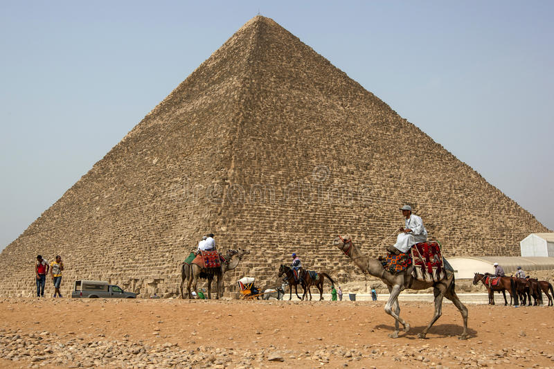 Egyptian camel and horse riders circle the base of the Pyramid of Khufu in Cairo in Egypt. This pyramid originally stood 146 metres high when it was completed stock photography