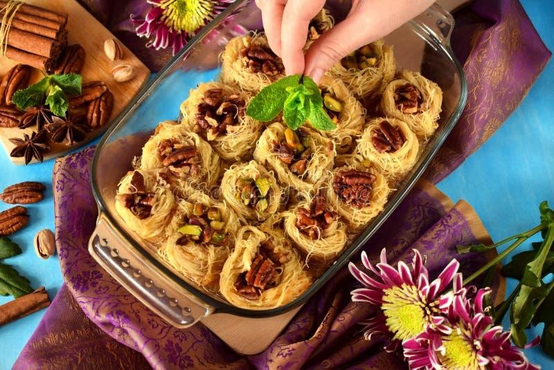 Egyptian dessert Kunafa made of kataifi dough with pistachio and pecan nuts stock photography