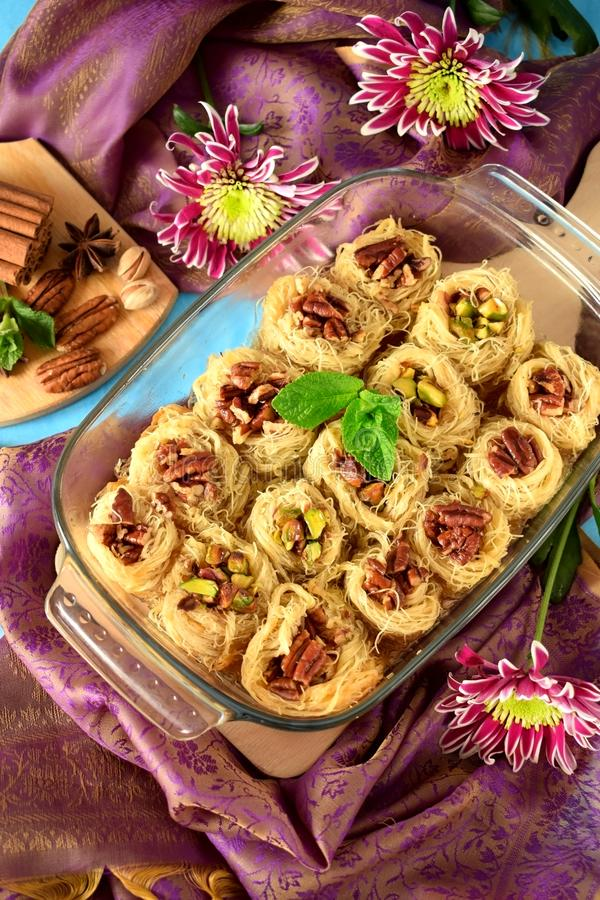 Egyptian dessert Kunafa made of kataifi dough with pistachio and pecan nuts royalty free stock photography