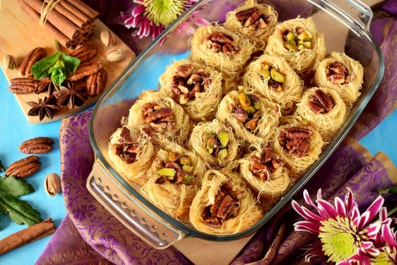 Egyptian dessert Kunafa made of kataifi dough with pistachio and pecan nuts royalty free stock photos
