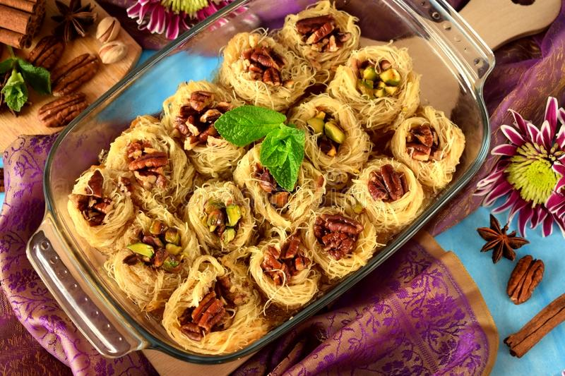 Egyptian dessert Kunafa made of kataifi dough with pistachio and pecan nuts royalty free stock images