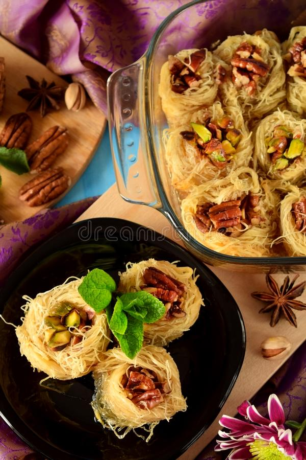 Egyptian dessert Kunafa made of kataifi dough with pistachio and pecan nuts in a glass baking dish. royalty free stock image
