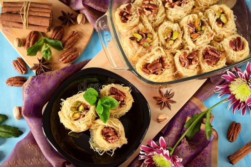 Egyptian dessert Kunafa with pistachio and pecan nuts stock photo