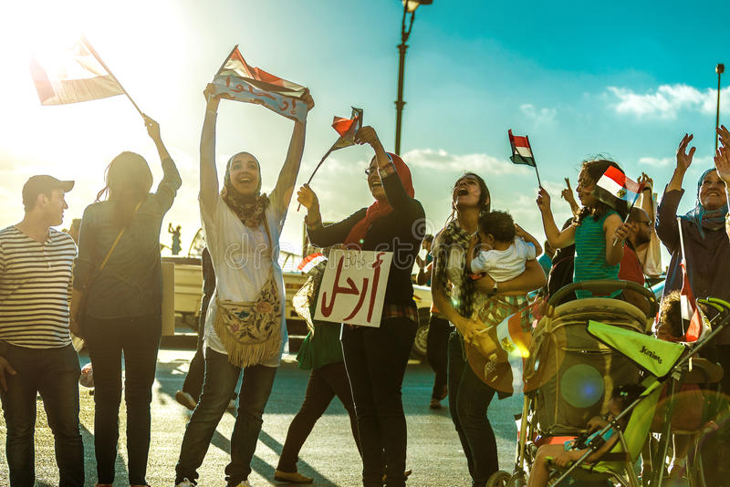 Egyptian Girls Protesting with Flags and LEAVE Sign stock image