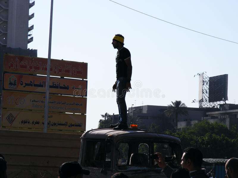 Egyptian guy tahrir square Egyptian revolution. Egyptian guy standing on an army truck and People gathering In tahrir square in egypt during Egyptian revolution royalty free stock images