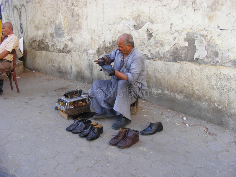 Shoeblack man cleaning shoes. Shoeshine poor old man in traditional Egyptian dress cleaner working cleaning shoes, Brushs shoemaker represents poverty stock images