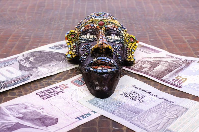 Egyptian mask lies at Egyptian pounds. royalty free stock photos