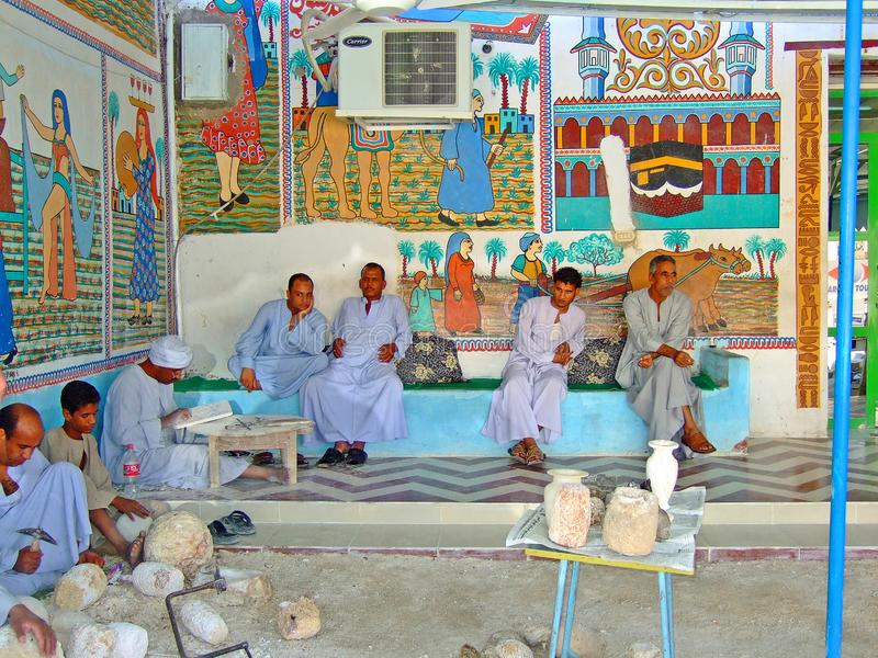 Egyptian men carving trinkets to sell to tourists in with a colourful mural wall royalty free stock photography