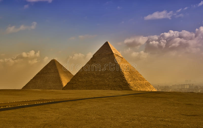 The Egyptian pyramids. Egyptian pyramids at Giza at dawn with an overcast sky royalty free stock photos