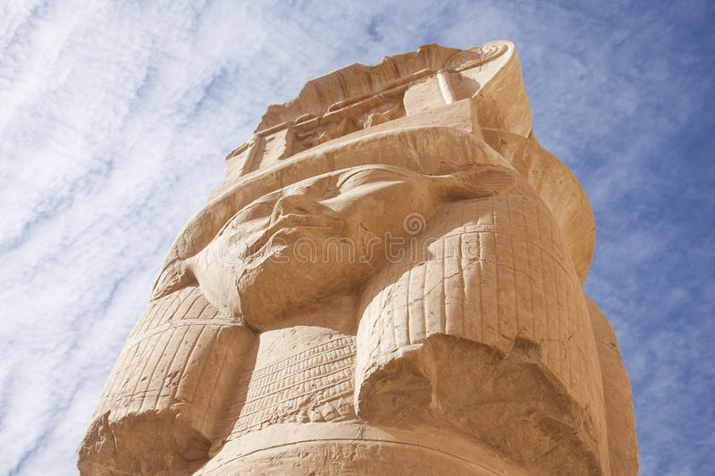 Egyptian statue. This picture shows a view of a huge Egyptian statue, looking up against the sky. There's only the head visible, with a female-like face in the royalty free stock image