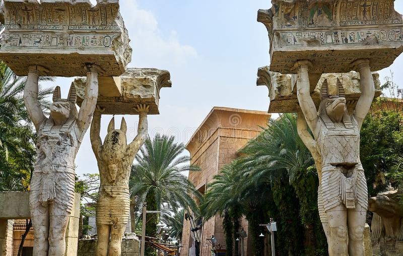 Egyptian statues lifting big boulders written with hieroglyphs at Unversal Studios Singapore stock image