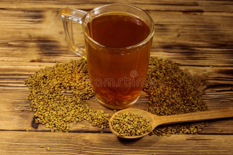Egyptian yellow tea or Methi Dana drink and fenugreek seeds on wooden table royalty free stock image