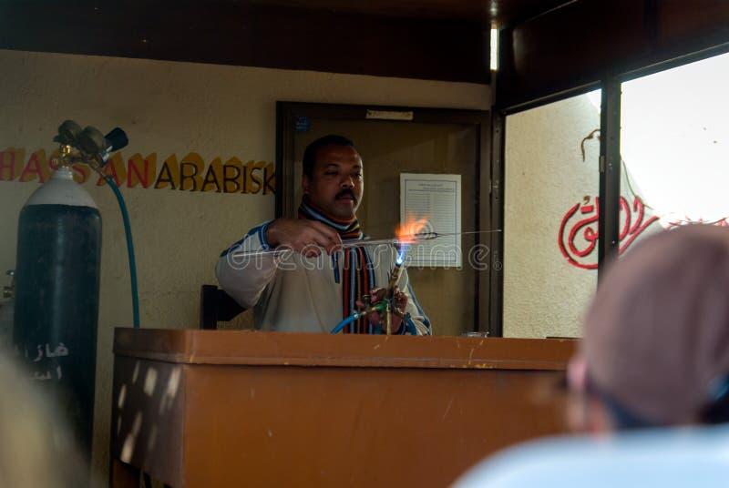 Egyptische artisanale die arbeider bij de deur van een parfumfabriek wordt gevestigd in het vormende glas van Aswan stock fotografie