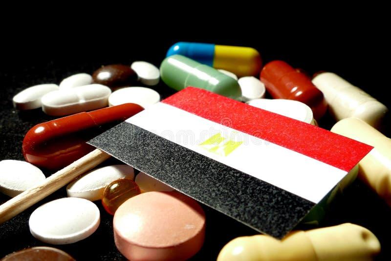 Egyptische vlag met partij van medische die pillen op zwarte backgr wordt geïsoleerd stock fotografie
