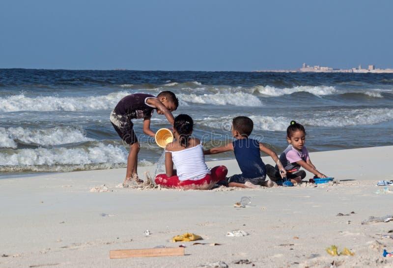 Egyptisk barnlek på stranden av medelhavet på Oktober 09, 2014 i Alexandria, Egypten Postrevolutionary kris r arkivfoto