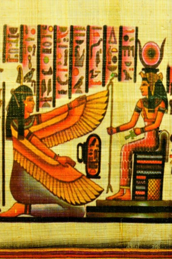 Egyptisk flicka för papyrus med vingar på hennes knä framme av linjalen royaltyfria foton
