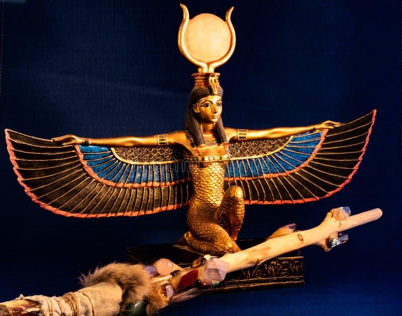 Egyptisk gudinnaIsis som knäfaller med den traditionella trollspöet som göras med kvarts, ametistkristaller, trä och fjädrar royaltyfri fotografi