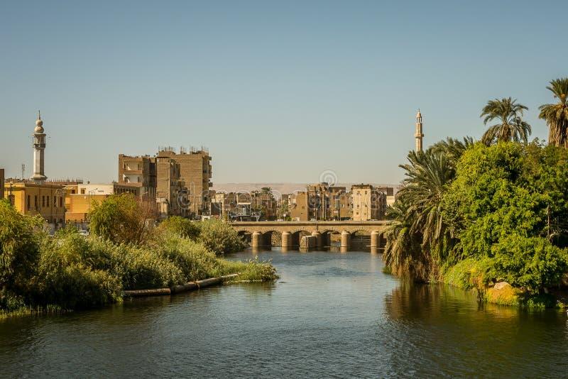 Egyptisk stad i solnedgången med två minaretes och en bro En sikt från en kryssning på flodNilen, Egypten Oktober 27, 2018 royaltyfri fotografi