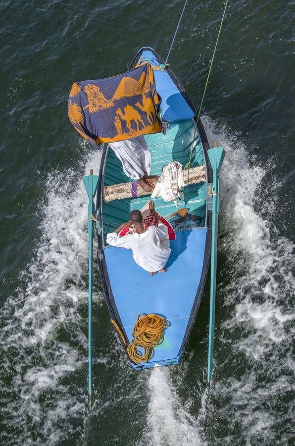 Egyptiska affärsmän som säljer strandhanddukar och borddukar till att passera kryssningskepp på Nilen royaltyfri bild