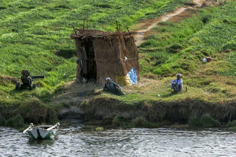 Egyptiska män kopplar av på banken av flodNilen i den sena eftermiddagen nära det Esna låset i Egypten royaltyfria bilder