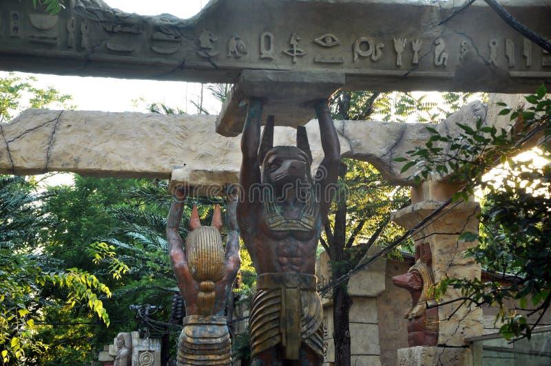 Egyptiska statyer och kolonner och palmträd landskap arkivfoton