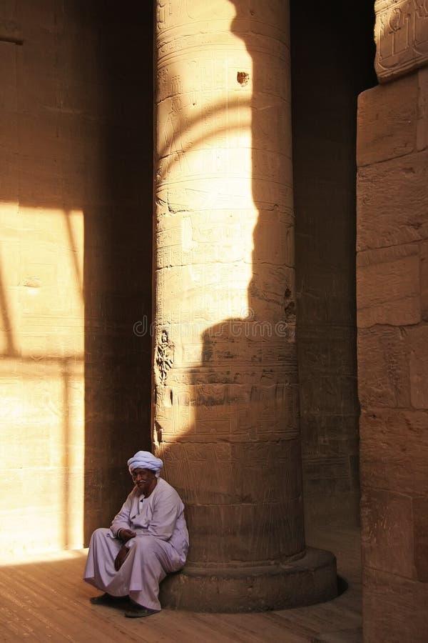 Egyptiskt mansammanträde vid kolonnen, Philae tempel arkivfoto