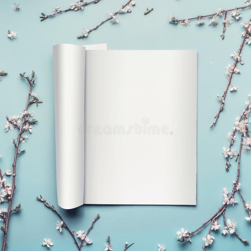 Egzamin próbny otwarty magazyn lub katalog na pastelowym błękitnym desktop tle z gałązkami i białym czereśniowym okwitnięciem zdjęcia royalty free