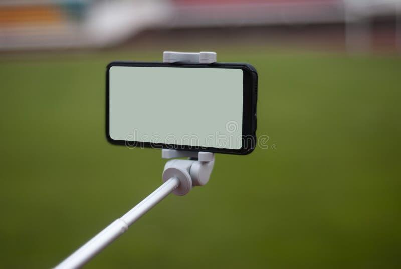 Egzamin próbny w górę czarnego smartphone z selfie kijem Bielu ekran dla projekta szablon na tle a zdjęcie royalty free