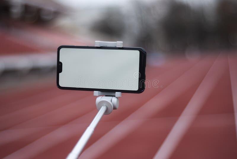 Egzamin próbny w górę czarnego smartphone z selfie kijem Bielu ekran dla projekta szablonu na tle czerwony ślad obrazy royalty free