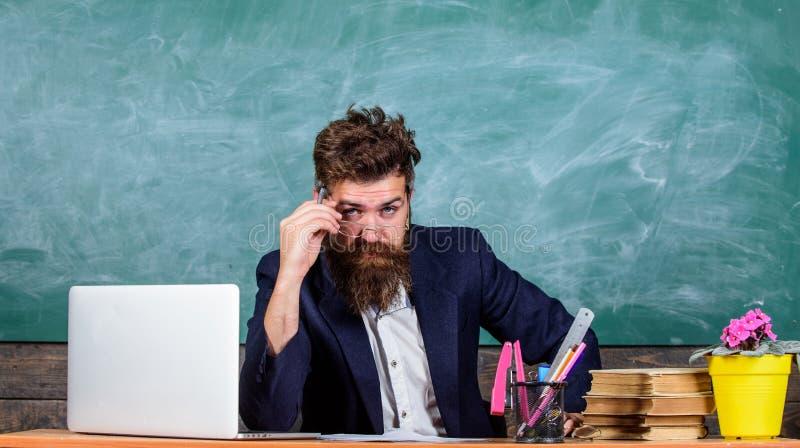 Egzaminator chytra twarz siedzi przy stołowym chalkboard tłem Examinator brodaty nauczyciel z eyeglasses zastanawiającą się twarz zdjęcie stock