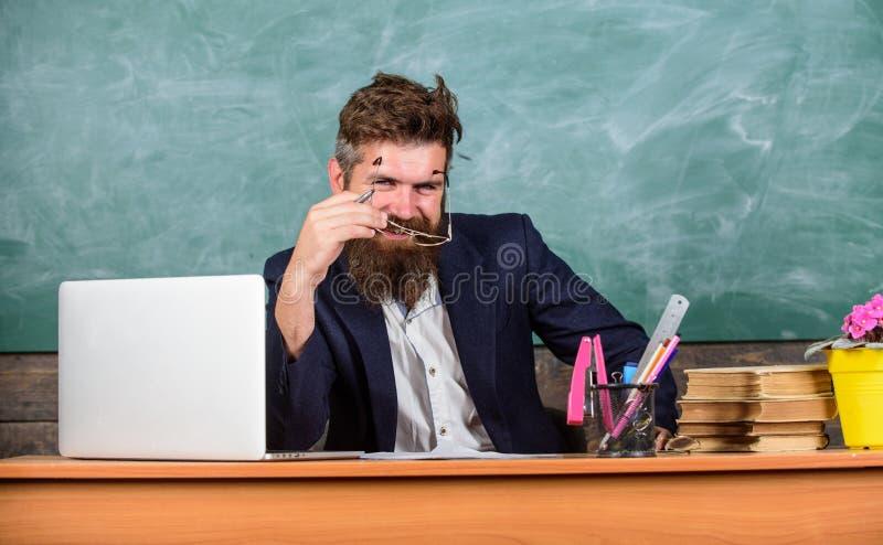 Egzaminator chytra twarz siedzi przy stołowym chalkboard tłem Szkolny egzaminu pojęcie Examinator brodaty nauczyciel z zdjęcie royalty free