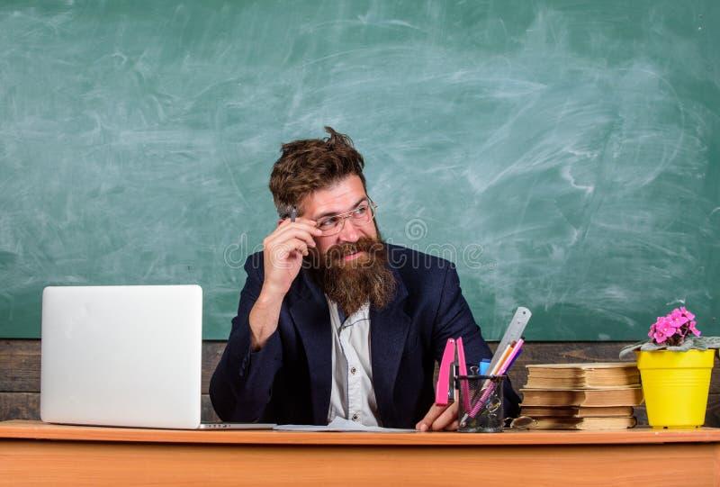 Egzaminator chytra twarz siedzi przy stołowym chalkboard tłem Szkolny egzaminu pojęcie Znał ty oszukiwał i dowód ja zdjęcia stock