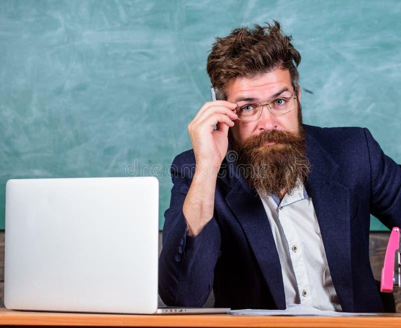 Egzaminator wątpienia pełno siedzi przy stołowym chalkboard tłem Chytry examinator ono waha się o ocenie Pewny wewnątrz fotografia stock