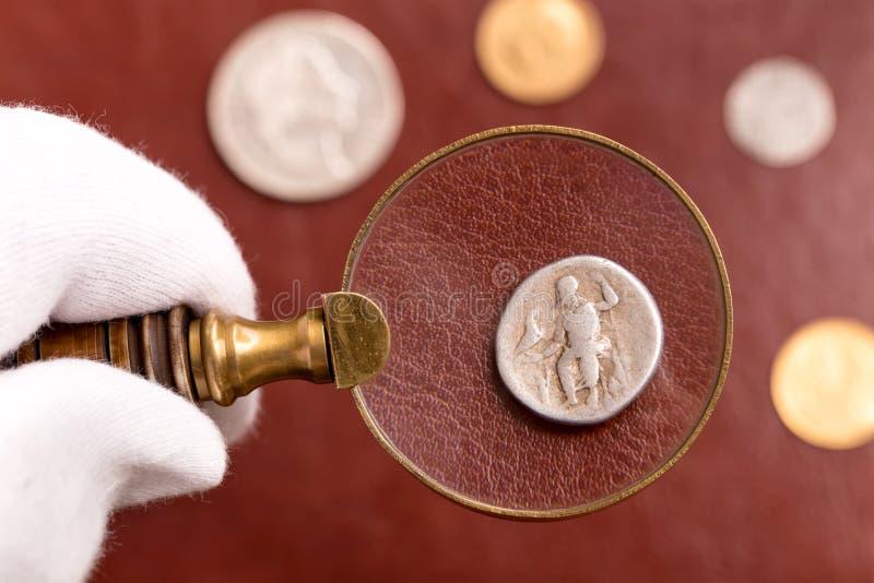 Egzamininować Romańską srebną monetę zdjęcie royalty free