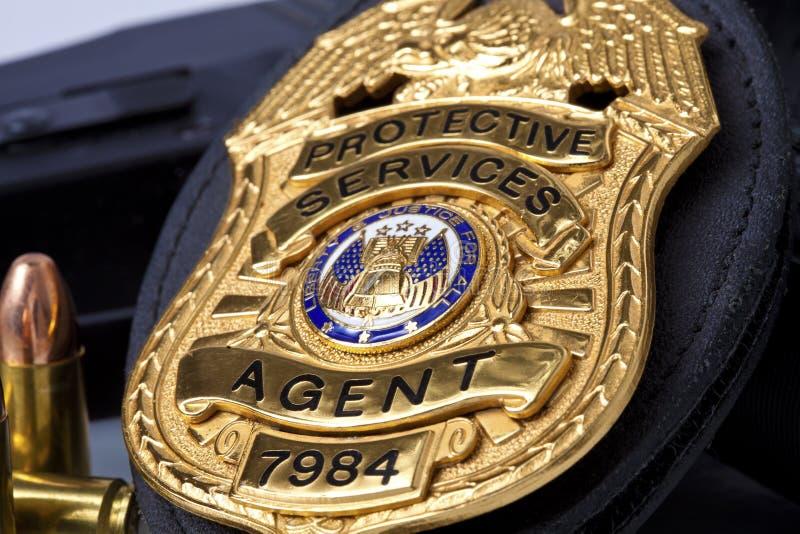 Egzekwowanie prawa odznaka z pistoletem, kajdankami i pociskami, obrazy royalty free