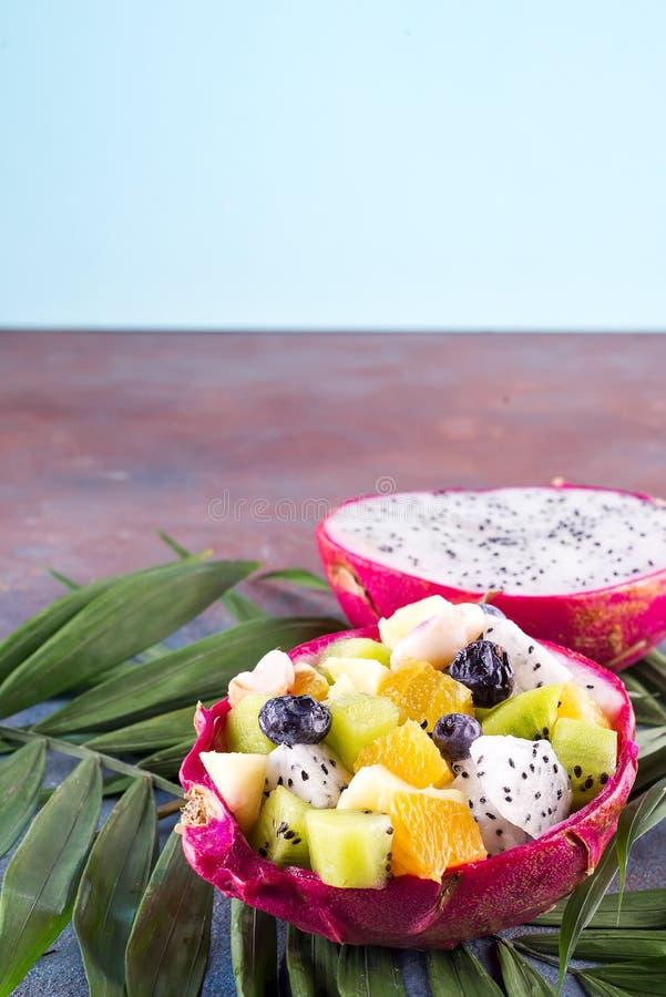 Egzotyczna owocowa sałatka słuzyć w połówce smok owoc na palmowych liściach na kamiennym tle, kopii przestrzeń zdjęcia stock