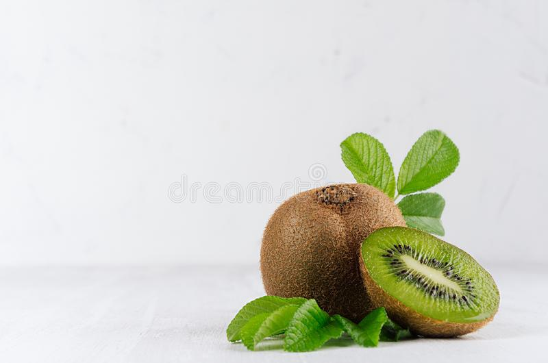 Egzotyczny owoc zbliżenie - soczysty dojrzały mięsisty kiwi z plasterkiem, opadowym sokiem i potomstwo zielenią, opuszcza w elega zdjęcie royalty free