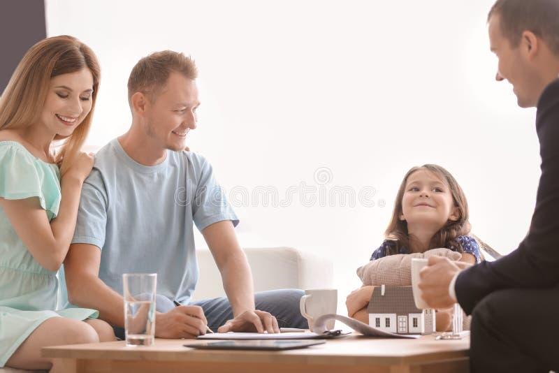 Ehemann, der einen Vertrag für kaufendes Haus im Büro des Immobilienmaklers unterzeichnet stockbild