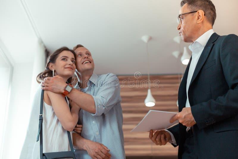 Ehemann, der Frau nach kaufender Hausstellung nahe Grundstücksmakler umarmt lizenzfreies stockfoto
