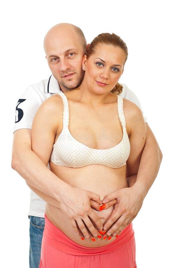 Ehemann, der seine schwangere Frau umfaßt stockfoto