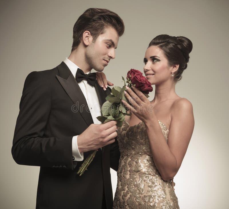 Ehemann, der seiner schönen Frau ein Bündel rote Rosen anbietet lizenzfreie stockfotos