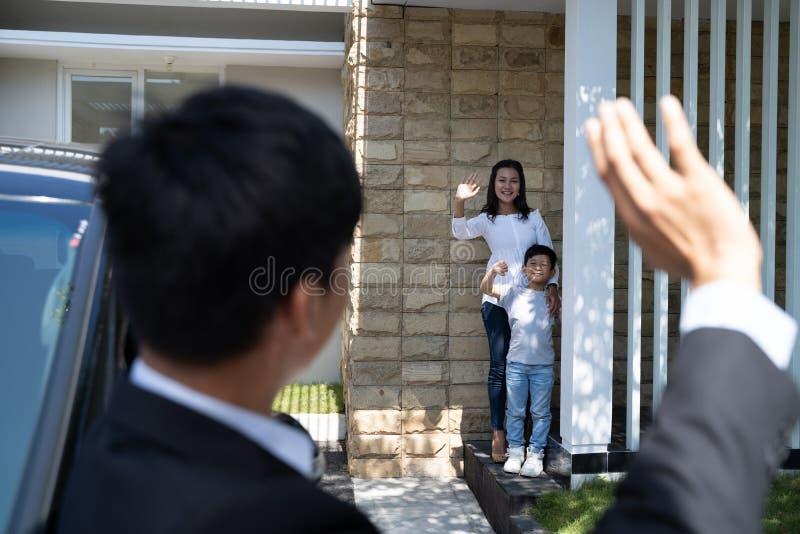 Ehemann, der zu seiner Familie bevor dem Gehen zu arbeiten zum Abschied winkt stockfoto