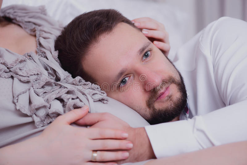 Ehemann, der zum Bauch seiner Frau hört lizenzfreies stockbild