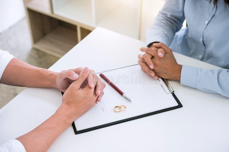 Ehemann und Frau lesen Scheidungsvereinbarung und unterzeichnende Scheidungsurteilauflösung oder Annullierung der Heiratarchivier lizenzfreie stockbilder