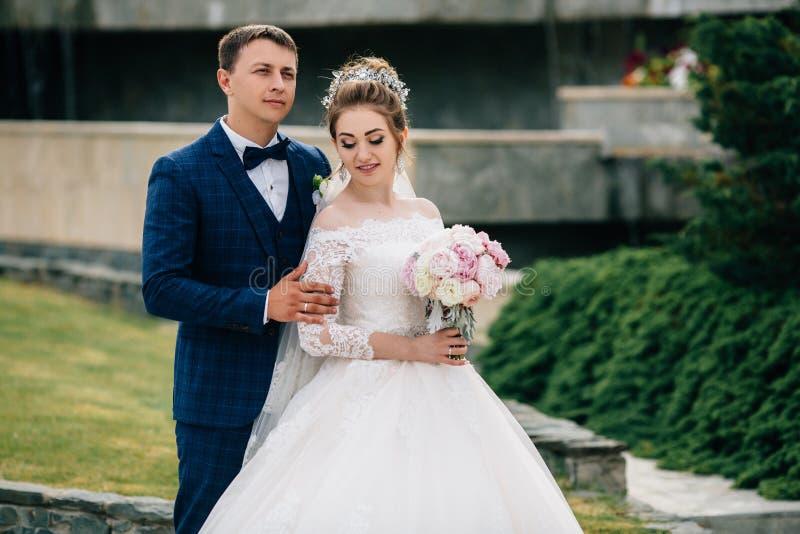Ehemann und Frau werfen auf der Straße auf Das Mädchen hält einen Blumenstrauß der Braut und schaut unten, der Kerl in lizenzfreies stockfoto