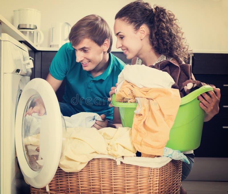 Ehemann, welche glücklicher Hausfrau hilft stockbild