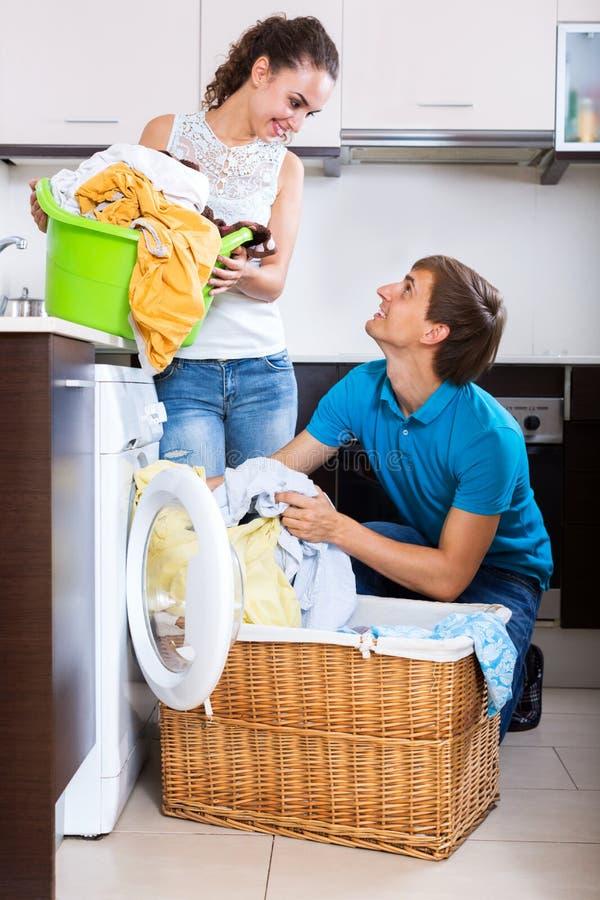Ehemann, welche glücklicher Hausfrau hilft lizenzfreies stockfoto